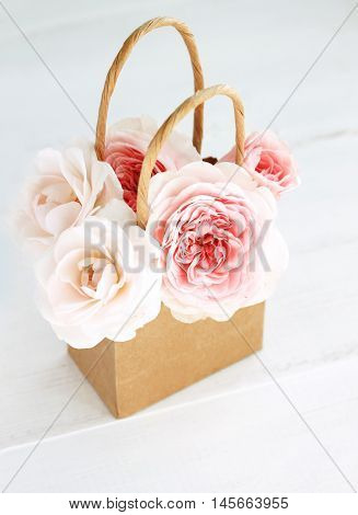 Little tender pink and white rose buds in craft paper shopping bag. Creamy toned present.