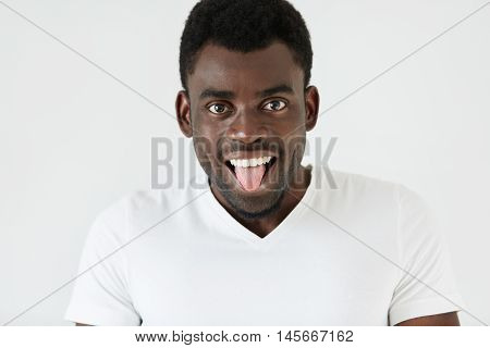 Human Face Expressions And Emotions. Body Language. Cheerful Funny Young African Man Wearing White T