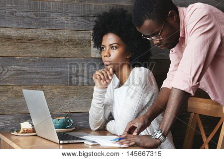 Attractive Dark-skinned Female Entrepreneur With Afro Haircut Sitting In Front Of Laptop Computer Wh