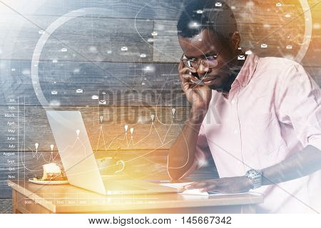 Visual Effects. Double Exposure Of Serious African Businessman In Glassess Working On Laptop With Th