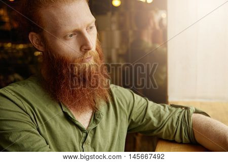 Cropped Portrait Of Caucasian Hipster Male Having Long Beard And Blue Eyes Sitting At Coffee Shop De