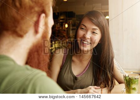 Unexpected Meeting: Young Female With Brunette Hair Having Nice Talk To Her Old Friend, Sitting With