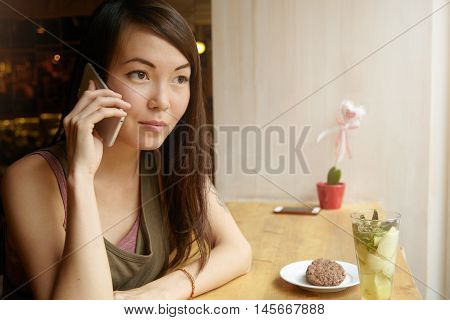Pretty Woman With Long Brunette Hair, Dressed Casually, Having Phone Conversation, Holding Electroni