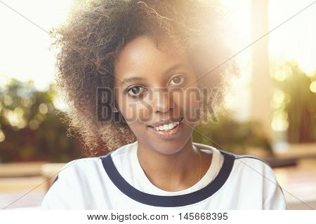 Flare Sun. Close Up Shot Of Young Good-looking Dark-skinned Female With Afro Haircut Wearing T-shirt