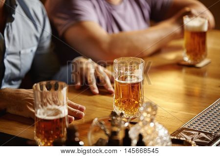 Friendly Talk In Club. Two Happy Young Men Chatting To Each Other While Drinking Lager Or Ale At Bar