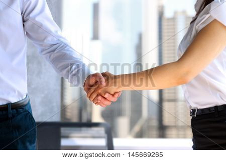 Close-up image of a firm handshake between two colleagues after signing contract