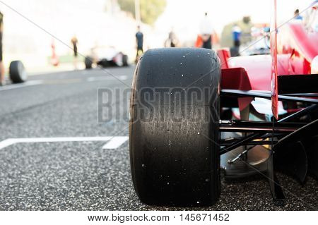 Black slick motorspor tire close up red car on starting grid with out of focus background