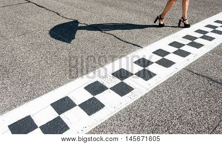 Woman sexy feet with high heels on motorsport chekered asphalt line