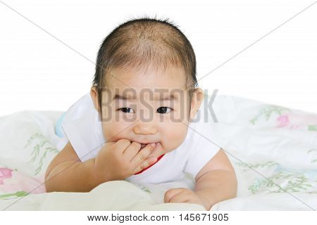 cute six months old baby lies in the bed at home and sucks his big finger