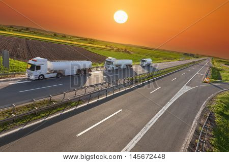 Three white gasoline tanker trucks in line driving towards the sun. Fast delivery on the freeway at beautiful sunset. Freight scene on the motorway near Belgrade Serbia.