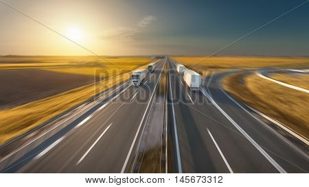 Delivery trucks driving towards the sun. Fast blurred motion image on the freeway in beautiful autumn scenery. Freight scene on the motorway near Belgrade Serbia.