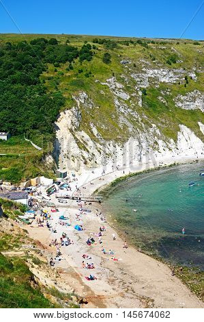 LULWORTH COVE, UNITED KINGDOM - JULY 19, 2016 - View looking down the hillside towards the cove with tourists enjoying the beach Lulworth Cove Dorset England UK Western Europe.