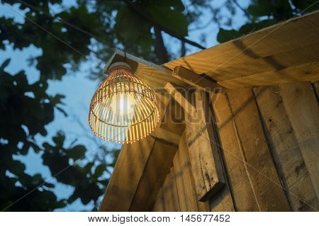 Decorating Lantern Hanging On Wooden Bar, A Lamp Made From Bamboo, Blurred Tree And Blue Sky In Back
