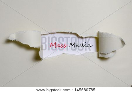 The word mass media appearing behind torn paper
