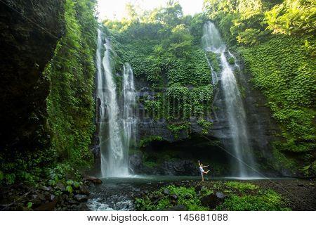 Woman Meditating Doing Yoga Between Waterfalls