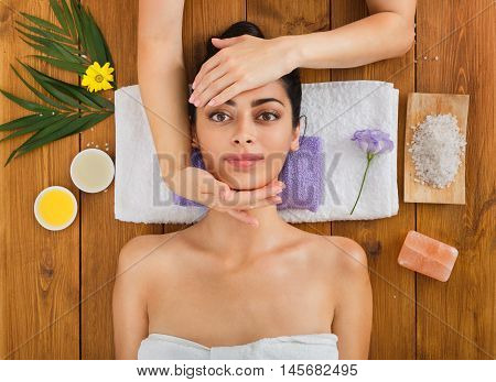 Head massage in spa. Young woman in wellness center. Professional cosmetologist make procedure to beautiful indian girl in beauty parlor. Top view on wood with aroma salt and other treatments