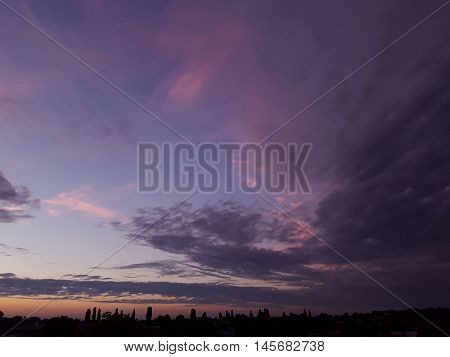 A Gorgeous Purple Clouds Sunset Sky With Storm Clouds Gathering At The Horizon