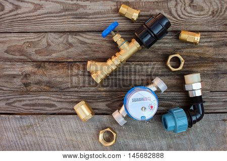 Plumbing equipment on the old wooden background.