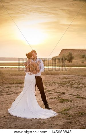 Wedding couple near the lake in the sunset light