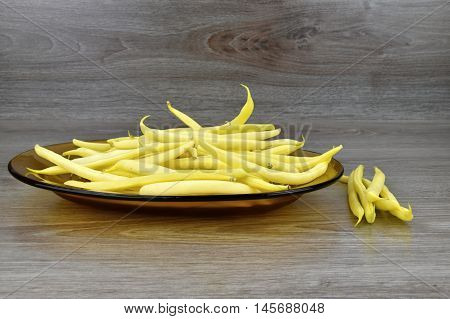 Yellow bean pods on the glass plate background wood