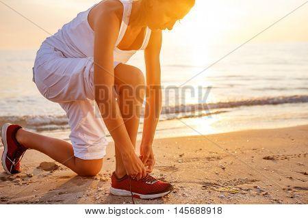 Caucasian woman jogging at seashore,  dressed in white