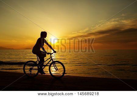 Woman On Vacation Biking At Beach