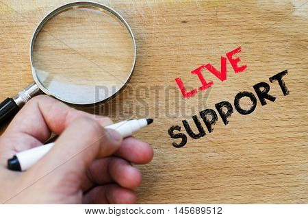 Live support text concept with human hand over wooden background