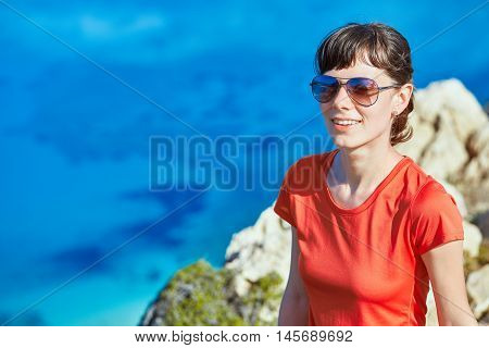 young woman doing sports workout on the cliff against sea and blue sky at early morning