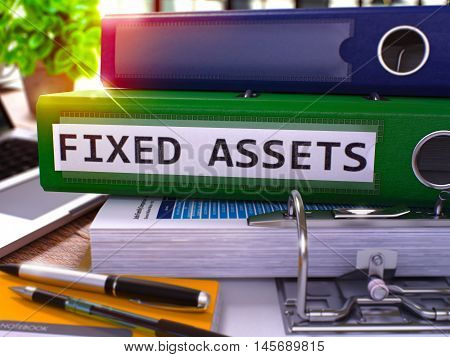 Green Office Folder with Inscription Fixed Assets on Office Desktop with Office Supplies and Modern Laptop. Fixed Assets Business Concept on Blurred Background. Fixed Assets - Toned Image. 3D.