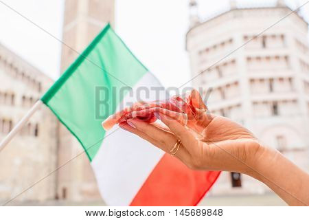 Holding prosciutto on the main square in Parma town with italian flag on the background in Italy. Parma is a city in the north of Italy famous for its prosciutto ham