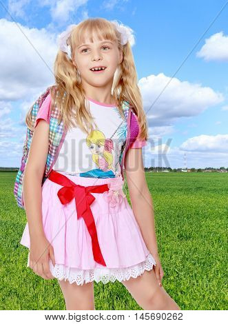 Happy little girl in a pink short skirt with a knapsack on his shoulders. Close-up.On the background of grass and blue sky with clouds.