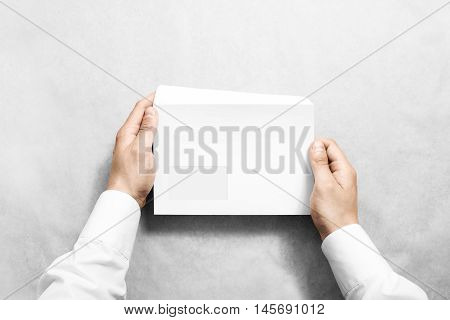 White blank envelope mock up holding in hand. Empty letter with transparent window design mockup. Message template presentation. Person opening clear mail.