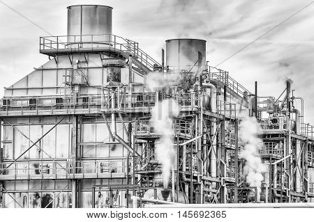 Chemical plant of a factory. Smokestacks pipes and tank. Black and white