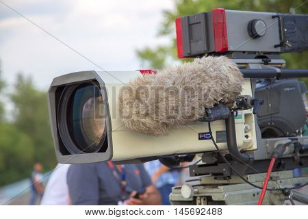 Professional video camera for recording sports programs. On the camera has a large microphone