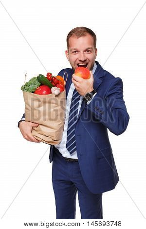 Handsome young businessman in suit holds shopping bag full of groceries and eats apple, isolated at white background. Healthy food shopping. Paper package with vegetables and fruits, happy male buyer.