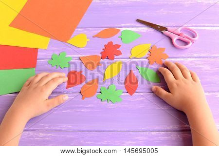 Child cut out of colored paper autumn leaves. Kid doing autumn paper crafts. Children hands, scissors on lilac wooden background. Hand made autumn diy for kids. Preschool education art and craft