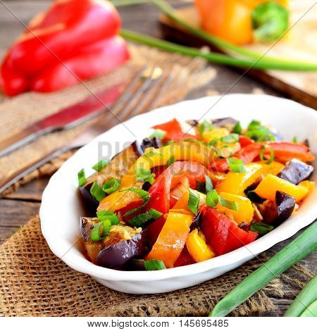 Stewed peppers with eggplant and garlic. Red and orange pepper stew with eggplant and garlic and topped with chopped green onions. Bright vegetable stew recipe. Closeup