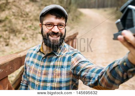 Young smiling photographer makes selfie on polaroid on a wooden bridge in a picturesque forest hipster life style trips