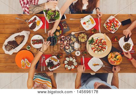 People eat healthy meals at served festive table served for party. Friends celebrate with organic food on wooden table top view. Men and women pass dishes to each other