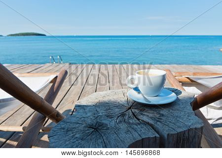 Wooden floor with chaise-longues and cup of coffee, Istria, Croatian coast