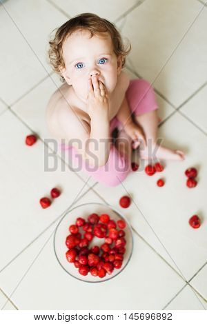 Cute little baby girl eats strawberries on the floor