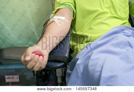 Close up Blood donor at donation and holding a bouncy ball in hand, selective focus, filtered image