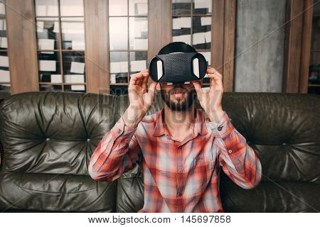 Young man wearing virtual reality glasses at home. Male preparing to enjoy innovational entertaining device - vr headset. Modern technology, innovation, cyberspace, entertainment concept