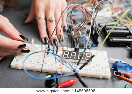 Woman engineer connecting led to breadboard. Electronics development, modern technologies, innovation, hobby concept