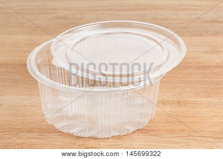 Empty round transparent plastic storage box of food package on wooden background