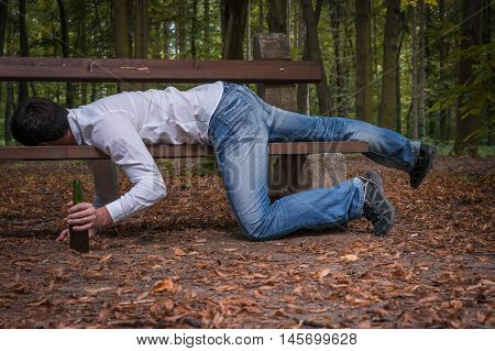 Drunk Man Asleep On A Park Bench With Beer Bottles