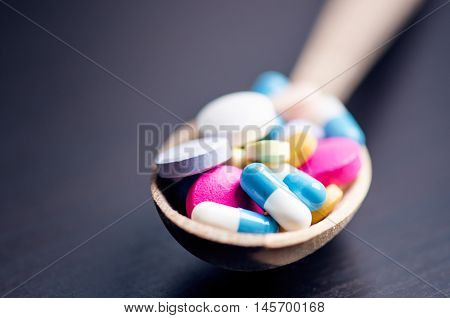 Full wooden spoon of pills. Pharmacy background on a black table. Tablets on a black background. Pills. Medicine and healthy. Close up of capsules. Differend kind of pills