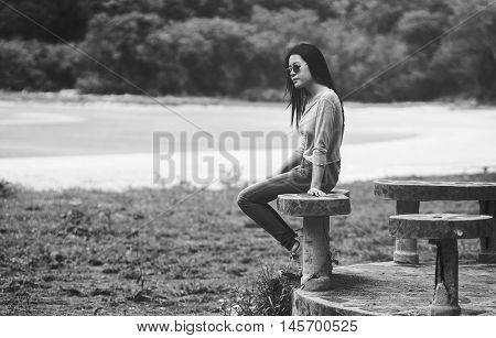 young asian woman wearing a sunglass sitting on marble chair near the beach , black and white, sad concept, selective focus
