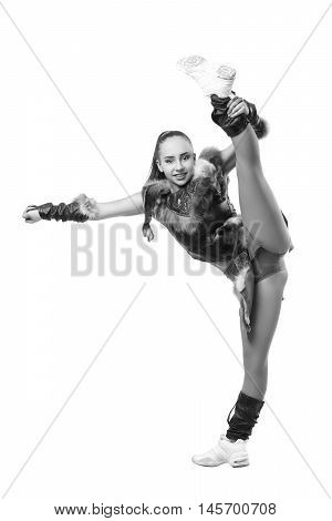 Young professional cheerleader dressed in a warrior costume stands in vertical splits. Black and white photography