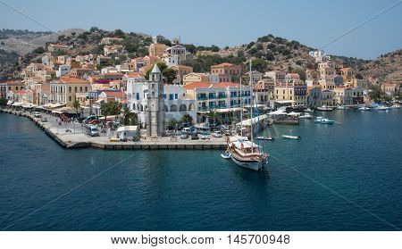 Symi Greece - August 1 2016: Panoramic image of Symi town with the harbor and the colorful houses on the hill in the Greek Island of Symi at the Aegean sea.